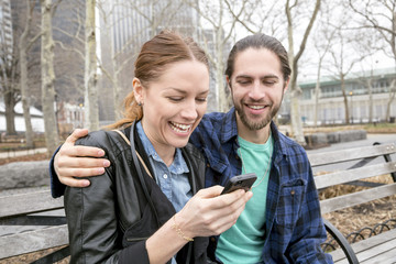 Couple checking messages on park bench, New York, New York, USA