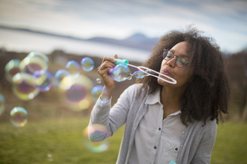 Mid adult woman blowing bubbles