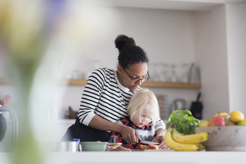 Mother helping son prepare food in kitchen