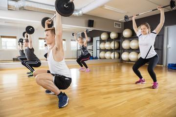 Determined Men And Women Lifting Dumbbells On Hardwood Floor