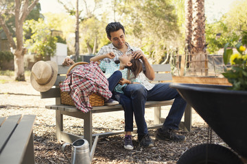 Mid adult man with hand on daughters forehead on community garden bench