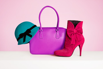 Woman fashion accessories. Green hat, purple bag and red short boots. Autumn Winter