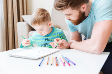 Son and dad drawing together on the table