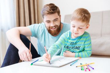 Happy little son and dad drawing with colorful markers