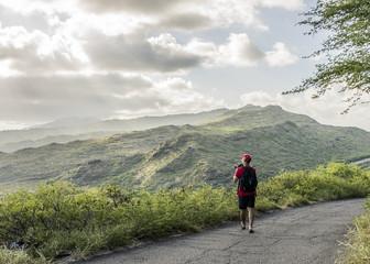Young male tourist photographing with digital SLR on Makapuu coast path, Oahu, Hawaii, USA