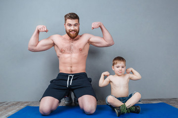 Cheerful father and his little son showing biceps