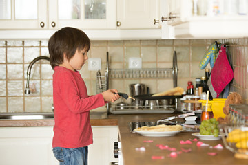 Sweet preschool child, helping his mom in the kitchen, making pa