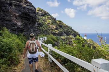 Rear view of young male tourist walking towards  Makapuu lighthouse, Oahu, Hawaii, USA