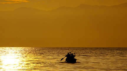 Wall Mural - Small boat with the fishermen sailing into the sunset on the Kazinga Channel. Africa. Uganda.