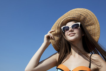 Beautiful girl in the sun hat enjoys sun