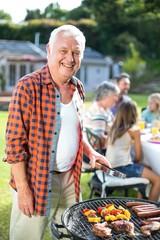 Portrait of senior man preparing food on barbecue