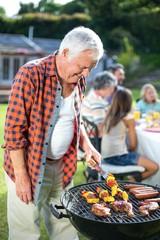 Happy senior man preparing food on barbecue