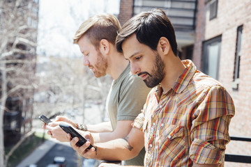 Male couple standing on balcony, looking at smartphones