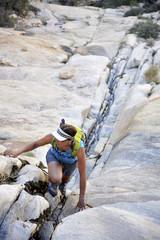 Young female rock climber climbing up crevice,  Mount Wilson, Nevada, USA