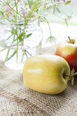 Green and red apples in jar and white flowers on table