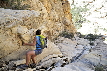Young female rock climber pulling herself up steep crevice,  Mount Wilson, Nevada, USA