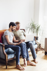 Male couple sitting on sofa, looking at laptop