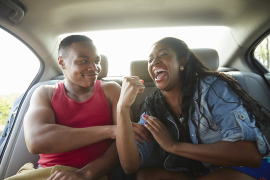 Young couple in car laughing, woman flexing muscles