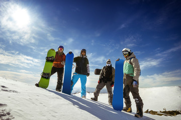 Group of snowboarders stands on the top of the mountain. Sheregesh resort, Siberia, Russia