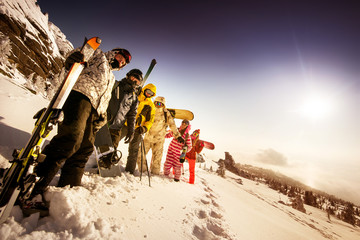 Group of friends skiers and snowboarders standing on the slope on background of valley. Sheregesh resort, Siberia, Russia