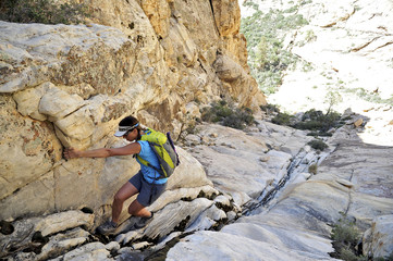 Young female rock climber pulling herself up crevice,  Mount Wilson, Nevada, USA