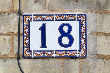 House Number 18 sign on wall