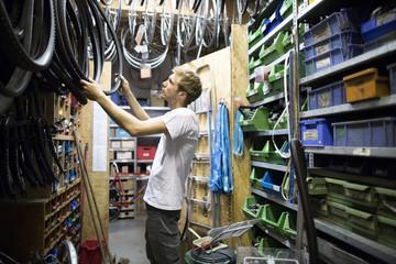 Mid adult man in repair shop choosing bicycle tyre