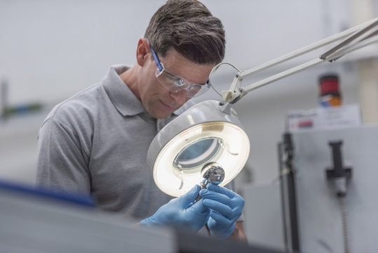 Engineer inspecting artificial hip joint in orthopaedic factory
