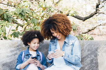 Mother and daughter sitting side by side looking at smartphones smiling