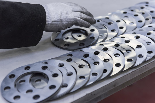 Engineers hand arranging cut parts in engineering factory, close up