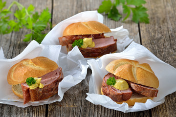 Street food bayerisch: Drei warme Leberkässemmeln mit Senf auf Wickelpapier mit Serviette - Bavarian street food: Three rolls with meat loaf and mustard on wrapping paper with white napkins