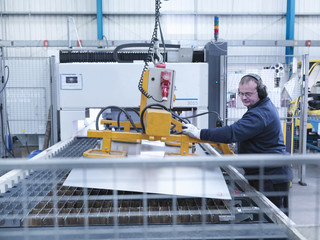 Engineer loading sheet metal into laser cutter in engineering factory