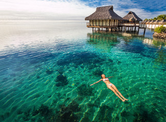 Woman in white bikini swimming in coral lagoon, Moorea, Tahiti