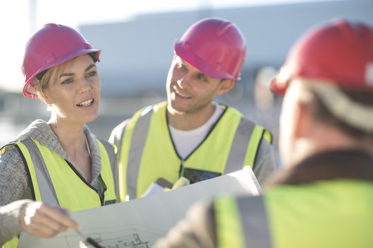 Architect and surveyors discussing blueprint on construction site