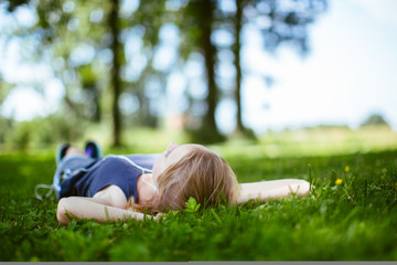 Young woman listening to music while lying on the grass