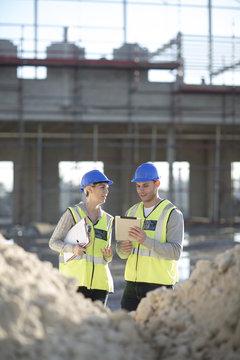 Surveyor using digital tablet talking to builder on construction site