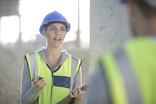 Female surveyor with clipboard talking to builder on construction site