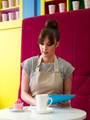 Young woman working in cake shop, taking working coffee break