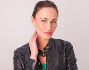 woman in leather jacket holding hand on neck