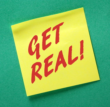 The phrase GET REAL! in red text on a yellow sticky note posted on a green notice board as a reminder