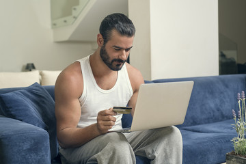 Man using a laptop while sitting on a sofa in his living room