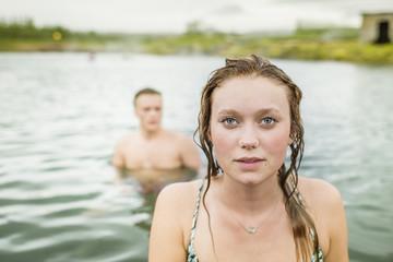 Portrait of young woman standing in front of boyfriend in Secret Lagoon hot spring (Gamla Laugin), Fludir, Iceland