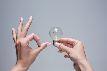 Hand holding an incandescent light bulb on gray background