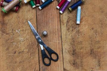 Forbici, ditale e spagnolette colorate su ripiano di legno