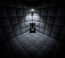 Dark cell in mental asylum with chair