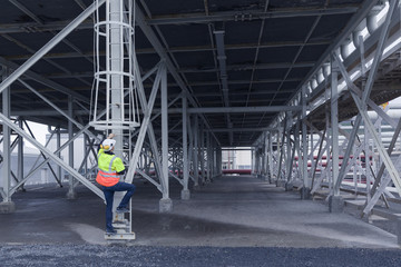 Engineer climbing ladder in warehouse space at geothermal power station