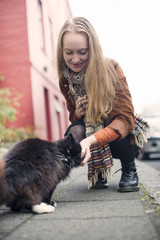 Young woman petting black cat on pavement