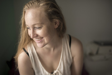 Portrait of young woman with freckles laughing