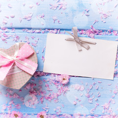 Gift  box with present in form of heart, petals of sakura pink f