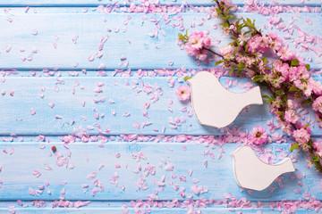 Tender pink  sakura flowers and two white wooden decorative bird